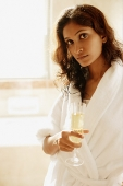 Woman in bathrobe, holding champagne glass, looking at camera - Asia Images Group