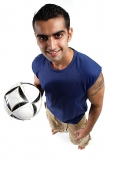 Young man holding soccer ball in one hand, looking at camera - Asia Images Group