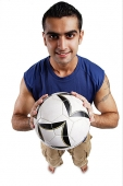 Young man holding soccer ball, looking at camera - Asia Images Group