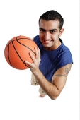 Young man holding  basketball, looking at camera - Asia Images Group