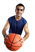 Young man holding basketball forward, looking at camera - Asia Images Group