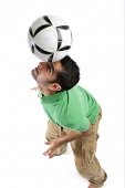 Young man balancing soccer ball on his head - Asia Images Group