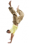 Young man doing handstand, looking at camera - Asia Images Group