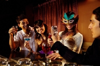 Couples at bar, with drinks and mobile phone. - Asia Images Group
