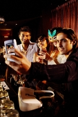 Couples at bar, taking picture with mobile phone camera - Asia Images Group