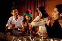 Couples at bar, having fun with noisemakers and mask - Asia Images Group