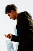Businessman using mobile phone, text messaging - Asia Images Group