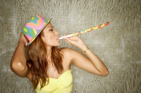 Young woman with party hat and noisemaker, portrait - Asia Images Group