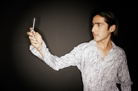 Young man looking at mobile phone, arms outstretched - Asia Images Group