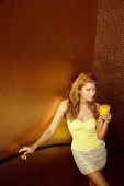 Young woman standing, holding drink, looking at camera - Asia Images Group
