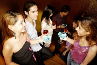 Young adults standing with drinks, talking - Asia Images Group