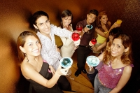 Young adults toasting with drinks, looking at camera - Asia Images Group