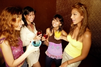 Four women with drinks, standing and talking - Asia Images Group