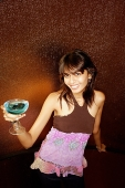 Young woman holding drink, smiling at camera - Asia Images Group