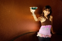 Young woman holding drink up towards camera - Asia Images Group