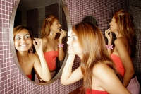 Two women in public restroom, looking at mirror, applying make-up - Asia Images Group
