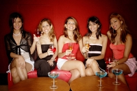 Women sitting in a row, holding drinks - Asia Images Group