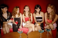 Women sitting side by side, holding drinks - Asia Images Group