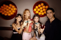 Young adults holding drinks out towards camera - Asia Images Group