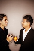 Young men with drinks, talking - Asia Images Group
