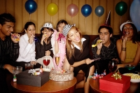 Young adults celebrating birthday, wearing party hats - Asia Images Group