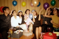 Young adults sitting side by side, celebrating, playing with balloons - Asia Images Group