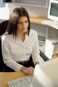 Female executive at desk, facing computer - Asia Images Group