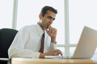 Male executive using laptop, hand on chin - Asia Images Group