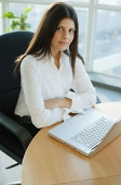 Female executive sitting, arms crossed, laptop in front of her - Asia Images Group