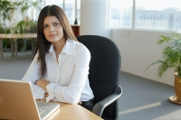 Female executive sitting in office, looking at camera, portrait - Asia Images Group