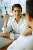 Female executive talking with man in front of her - Asia Images Group
