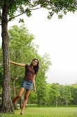 Young woman standing with hand on tree, smiling at camera - Asia Images Group