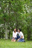 Couple in park, sitting, both looking away - Asia Images Group