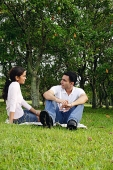Couple in park, sitting on grass - Asia Images Group