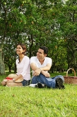 Couple in park, sitting on grass, looking away - Asia Images Group
