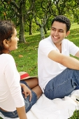 Couple in park, sitting on picnic blanket, looking at each other - Asia Images Group