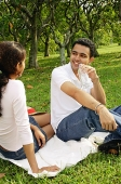 Couple sitting on picnic blanket, facing each other, man drinking from water bottle - Asia Images Group
