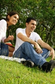 Couple sitting on grass, looking away - Asia Images Group