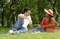 Couple in park, sitting on grass, having picnic - Asia Images Group