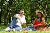 Couple in park, sitting on grass, having picnic, looking at camera - Asia Images Group