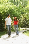 Couple in park, walking, holding hands - Asia Images Group