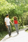 Couple in park, holding hands and walking - Asia Images Group