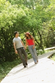Couple holding hands and walking in park - Asia Images Group