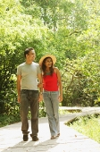 Man and woman walking side by side in park - Asia Images Group