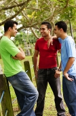 Young men standing, talking - Asia Images Group