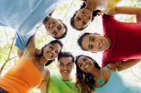 Group of young adults arms around each other, looking down at camera - Asia Images Group