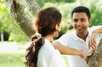 Couple smiling at each other, standing on either side of tree - Asia Images Group