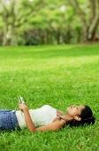 Young woman listening to music with headphones, lying on grass - Asia Images Group