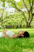 Young woman lying on grass, listening to music with headphones - Asia Images Group