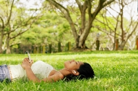 Young woman lying on grass with headphones - Asia Images Group